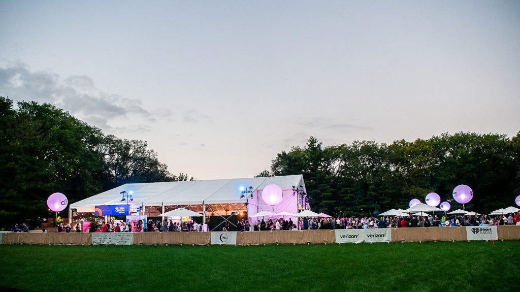 Large outdoor social event with a tent